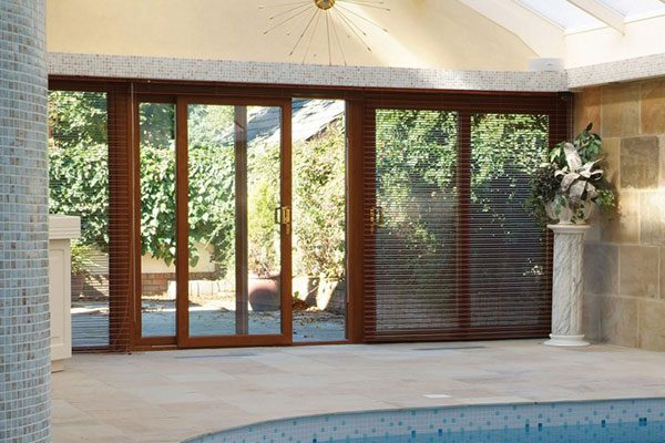 Timber sliding doors opening onto indoor swimming pool and onto patio