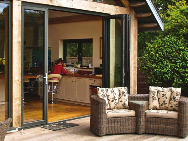 bi-folding patio doors opening onto garden with decking and trees