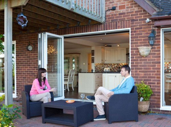 couple relaxing on patio next to new bi-fold doors